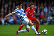 Yoon Suk-Young of QPR battles for the ball with Steven Gerrard of Liverpool during the Barclays Premier League match between Queens Park Rangers and Liverpool at Loftus Road on October 19, 2014 in London, England.