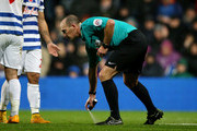 Referee Mike Dean uses vanishing spray during the Barclays Premier League match between Queens Park rangers and Manchester City at Loftus Road on November 8, 2014 in London, England.