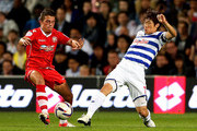 Ji Sung Park of QPR (R) in action with Florent Cuvelier of Walsall during the Capital One Cup Second Round match between Queens Park Rangers and Walsall at Loftus Road on August 28, 2012 in London, England.