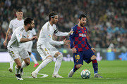 Lionel Messi of FC Barcelona controls the ball under pressure from Sergio Ramos of Real Madrid and Daniel Carvajal of Real Madrid during the Liga match between Real Madrid CF and FC Barcelona at Estadio Santiago Bernabeu on March 01, 2020 in Madrid, Spain.