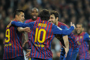Cesc Fabregas (R), Lionel Messi (C) and Alexis Sanchez of FC Barcelona celebrate the goal of their teammate Eric Abidal during the Copa del Rey quarter final match between Real Madrid and Barcelona at Estadio Santiago Bernabeu on January 18, 2012 in Madrid, Spain.