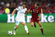 Luka Modric of Real Madrid CF competes for the ball with Adam Lallana of Liverpool during the UEFA Champions League final between Real Madrid and Liverpool on May 26, 2018 in Kiev, Ukraine.