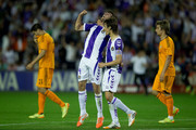 Alvaro Rubio (R) of Real Valladolid CF celebrates their tie with his teammate Marc Valiente (L) as Alvaro B. Morata (L) and Fabio Coentrao (R) of Real Madrid CF leave the pitch after the La Liga match between Real Valladolid CF and Real Madrid CF at Estadio Jose Zorilla on May 7, 2014 in Valladolid, Spain.