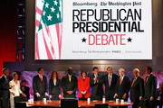 (L-R) Republican Presidential hopefuls Jon Huntsman, U.S. Rep. Michele Bachmann (R-MN), Texas Gov. Rick Perry, moderator Julianna Goldman, Herman Cain, moderator Karen Tumulty, Mitt Romney, moderator Charlie Rose, U.S. Rep. Ron Paul (R-TX), Newt Gingrich and Rick Santorum gather prior to the start of the Republican Presidential debate hosted by Bloomberg and the Washington Post on October 11, 2011 at Dartmouth College in Hanover, New Hampshire. Eight GOP candidates met for the first debate of the 2012 campaign focusing solely on the economy.