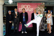"""(L-R) President and CEO of AEG Live Randy Phillips, Caesars Palace President Gary Selesner, Stiefel Entertainment CEO Arnold Stiefel and Co-CEO and President of AEG Live/Concerts West John Meglen look on as recording artist Rod Stewart kicks a soccer ball to the crowd as he is introduced at Caesars Palace to launch his two-year residency """"Rod Stewart: The Hits."""" at The Colosseum August 24, 2011 in Las Vegas, Nevada."""