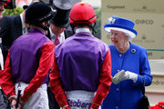 Queen Elizabeth II speaks with her riders, jockeys   Jamie Spencer (L) and Sean Levey in the parade ring ahead of the Sandringham Handicap Stakes during Royal Ascot 2015 at Ascot racecourse on June 17, 2015 in Ascot, England.