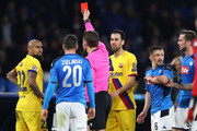 Arturo Vidal (L) of Barcelona is shown a red card by referee Mark Borsch of Germany during the UEFA Champions League round of 16 first leg match between SSC Napoli and FC Barcelona at Stadio San Paolo on February 25, 2020 in Naples, Italy.