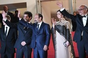 """Iranian director Asghar Farhadi (C) waves as he arrives on May 21, 2016 with French producer and distributor Alexandre Mallet-Guy (L), Iranian actor Shahab Hosseini (2ndL), Iranian actress Taraneh Alidoosti (2ndR) and Iranian actor Babak Karimi, for the screening of the film """"The Salesman (Forushande)"""" at the 69th Cannes Film Festival in Cannes, southern France.  / AFP / ANNE-CHRISTINE POUJOULAT"""