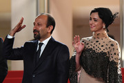 """Iranian director Asghar Farhadi (L) and Iranian actress Taraneh Alidoosti wave as they arrive on May 21, 2016 for the screening of the film """"The Salesman (Forushande)"""" at the 69th Cannes Film Festival in Cannes, southern France.  / AFP / ANNE-CHRISTINE POUJOULAT"""