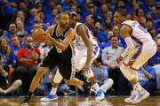 Tony Parker #9 of the San Antonio Spurs handles the ball against Kevin Durant #35 and Russell Westbrook #0 of the Oklahoma City Thunder in the third quarter during Game Three of the Western Conference Finals of the 2014 NBA Playoffs at Chesapeake Energy Arena on May 25, 2014 in Oklahoma City, Oklahoma.