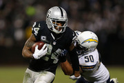 Safety Charles Woodson #24 of the Oakland Raiders is tackled by linebacker Manti Te'o #50 of the San Diego Chargers in the fourth quarter at O.co Coliseum on December 24, 2015 in Oakland, California.