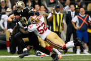 Jimmy Graham #80 of the New Orleans Saints tries to break a tackle by Patrick Willis #52 of the San Francisco 49ers at Mercedes-Benz Superdome on November 17, 2013 in New Orleans, Louisiana.
