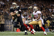 Jimmy Graham #80 of the New Orleans Saints is brought down by Chris Borland #50 of the San Francisco 49ers during the third quarter of a game at the Mercedes-Benz Superdome on November 9, 2014 in New Orleans, Louisiana.