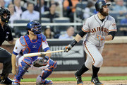 Brandon Belt #9 of the San Francisco Giants flies out to Austin Jackson of the New York Mets as Devin Mesoraco #29 of the New York Mets defends at home plate in the second inning on August 20, 2018 at Citi Field in the Flushing neighborhood of the Queens borough of New York City.