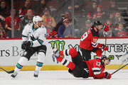 Evander Kane #9 of the San Jose Sharks trips up Nico Hischier #13 of the New Jersey Devils during the third period at the Prudential Center on October 14, 2018 in Newark, New Jersey. The Devils defeated the Sharks 3-2.