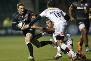 Chris Ashton of Saracens is tackled by Mark Easter and Nick Macleod of Sale Sharks during the European Rugby Champions Cup pool one match between Saracens and Sale Sharks at Allianz Park on December 13, 2014 in Barnet, England.