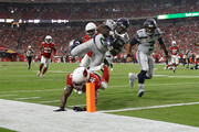 Running back Mike Davis #27 of the Seattle Seahawks scores a 20-yard touchdown over defensive back Antoine Bethea #41 of the Arizona Cardinals during the first quarter at State Farm Stadium on September 30, 2018 in Glendale, Arizona.