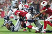Running back David Johnson #31 of the Arizona Cardinals fumbles after being hit by linebacker Mychal Kendricks #56, cornerback Tre Flowers #37 and defensive back Bradley McDougald #30 of the Seattle Seahawks during the first quarter at State Farm Stadium on September 30, 2018 in Glendale, Arizona.