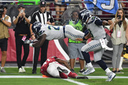 Running back Mike Davis #27 of the Seattle Seahawks scores a 20-yard touchdown run over defensive back Antoine Bethea #41 of the Arizona Cardinals during the first quarter at State Farm Stadium on September 30, 2018 in Glendale, Arizona.