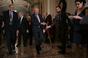 Senate Minority Leader Harry Reid (D-NV) (C) hands his cane to a staff member before talking to reporters following the weekly Senate Democratic policy luncheon at the U.S. Capitol September 13, 2016 in Washington, DC. Reid repeated his call on the Senate Republicans in the majority to allow a vote for funding to fight against the Zika virus and to pass a federal budget continuing resolution.