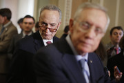 Sen. Charles Schumer (D-NY) (C) look sover the shoulder of Senate Majority Leader Harry Reid (D-NV) as he talks to reporters following the weekly Senate Democratic policy luncheon at the U.S. Capitol November 3, 2015 in Washington, DC. Senate Democrats called for an omnibus federal budget bill after newly-elected Speaker of the House Paul Ryan (R-WI) said he would open the legislative process to allow riders that could attach provisions to the bill that could hurt its chances of passing.
