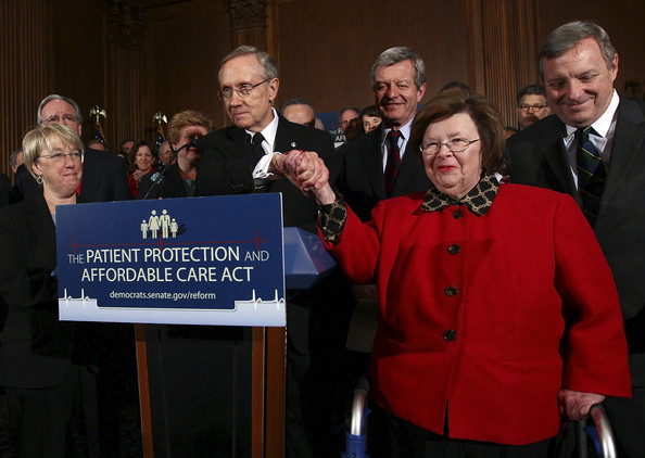 Senate Majority Leader Harry Reid (D-NV) shakes hands with Sen. Barbara Mikulski (D-MD) who cast the 60th vote in a final series of procedural votes on pending healthcare legislation in the U.S. Senate December 23, 2009 in Washington, DC.  The U.S. Senate is expected to vote on final passage of their national healthcare legislation tomorrow, Christmas Eve.