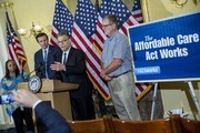Sen. Al Franken (D-MN) speaks next to Vanita Johnson (L) and Terry Donald (R), both beneficiaries of the Affordable Care Act, and Sen. Chris Murphy (D-CT) (2nd L) at a news conference to discuss the Affordable Care Act case being heard at the Supreme Court, March 4, 2015 on Capitol Hill in Washington, DC. Today the Supreme Court was scheduled to hear oral arguments in the case of King v. Burwell that could determine the fate of health care subsidies for as many as eight million people.