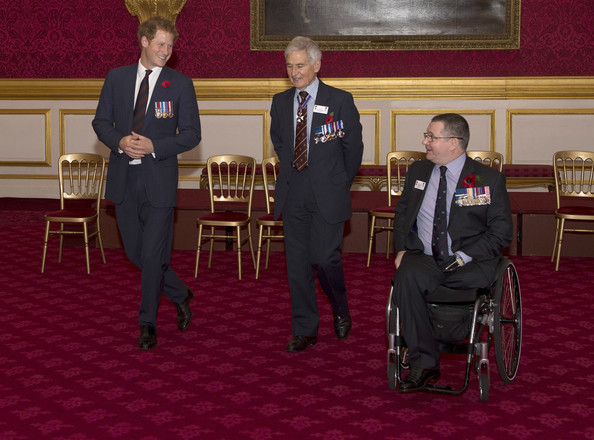 Prince Harry chats with Jim Beaton GC (former Royal Protection officer) and Major Peter Norton GC (R) as he hosts the President's Party in remembrance and re-dedication for members of the Victoria Cross and George Cross Association in the State Apartments at St James's Palace on October 29, 2014 in London, England.