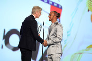 Arsene Wenger preents the Laureus World Sportsman of the Year award to British F1 driver Lewis Hamilton on stage during the 2020 Laureus World Sports Awards at Verti Music Hall on February 17, 2020 in Berlin, Germany.