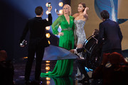 Orlando Bloom (L) photographs with a smartphone host Barbara Schoeneberger and Irina Shayk on stage during the GQ Men of the Year Award show at Komische Oper on November 08, 2018 in Berlin, Germany.