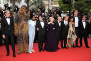 """(L-R) Paul Bettany, Chewbacca (in costume), Donald Glover, Alden Ehrenreich, Emilia Clarke, director Ron Howard, Woody Harrelson, Thandie Newton, Joonas Suotam and producer Simon Emanuel attends the screening of """"Solo: A Star Wars Story"""" during the 71st annual Cannes Film Festival at Palais des Festivals on May 15, 2018 in Cannes, France."""