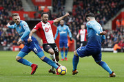Southampton's English midfielder Nathan Redmond (C) vies with Arsenal's Welsh midfielder Aaron Ramsey (L) and Arsenal's German midfielder Mesut Ozil during the English Premier League football match between Southampton and Arsenal at St Mary's Stadium in Southampton, southern England on December 10, 2017. / AFP PHOTO / Adrian DENNIS / RESTRICTED TO EDITORIAL USE. No use with unauthorized audio, video, data, fixture lists, club/league logos or 'live' services. Online in-match use limited to 75 images, no video emulation. No use in betting, games or single club/league/player publications.  /