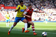 Luke Shaw of Southampton holds off the challenge of Hatem Ben Arfa of Newcastle during the Barclays Premier League match between Southampton and Newcastle United at St Mary's Stadium on March 29, 2014 in Southampton, England.
