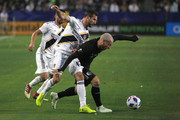 Chris Pontius #19 of the Los Angeles Galaxy compete for the ball with Yohan Croizet #10 of Sporting Kansas CIty at StubHub Center on April 8, 2018 in Carson, California.
