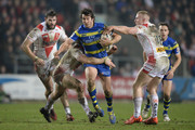 Stefan Ratchford of Warrington Wolves is tackled by Kyle Amor and Luke Thompson of St Helens during the First Utility Super League match between St Helens and Warrington Wolves at Langtree Park on March 19, 2015 in St Helens, England.