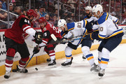 Jordan Martinook #48 and Nick Cousins #25 of the Arizona Coyotes attempt to control the puck under pressure from Alex Pietrangelo #27 and Brayden Schenn #10 of the St. Louis Blues during the third period of the NHL game at Gila River Arena on March 31, 2018 in Glendale, Arizona.