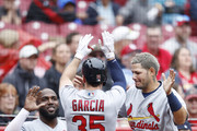 Greg Garcia #35 of the St. Louis Cardinals is congratulated by Yadier Molina #4 and Marcell Ozuna #23 after hitting a solo home run in the second inning of the game against the Cincinnati Reds at Great American Ball Park on April 14, 2018 in Cincinnati, Ohio.