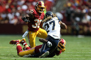 Running back Tre Mason #27 of the St. Louis Rams is tackled by cornerback DeAngelo Hall #23 of the Washington Redskins while strong safety Kyshoen Jarrett #30 of the Washington Redskins defends in the second quarter of a game at FedExField on September 20, 2015 in Landover, Maryland.