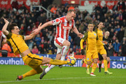 Charlie Adam of Stoke City is tackled by Lewis Dunk of Brighton and Hove Albion during the Premier League match between Stoke City and Brighton and Hove Albion at Bet365 Stadium on February 10, 2018 in Stoke on Trent, England.