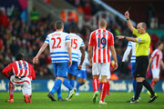 Referee Mike Dean shows Victor Moses of Stoke City (L) a yellow card for diving during the Barclays Premier League match between Stoke City and Queens Park Rangers at Britannia Stadium on January 31, 2015 in Stoke on Trent, England.