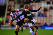 Patrice Evra of Manchester United tussles with Sebastian Larsson of Sunderland during the Capital One Cup Semi-Final, first leg match between Sunderland and Manchester United at Stadium of Light on January 7, 2014 in Sunderland, England.