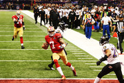 Colin Kaepernick #7 of the San Francisco 49ers runs into the endzone for a 15-yard rushing touchdown in the fourth quarter as teammate Joe Staley #74 against the Baltimore Ravens during Super Bowl XLVII at the Mercedes-Benz Superdome on February 3, 2013 in New Orleans, Louisiana.