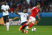 Admir Mehmedi of Switzerland is tackled by Patrice Evra of France during the UEFA EURO 2016 Group A match between Switzerland and France at Stade Pierre-Mauroy on June 19, 2016 in Lille, France.