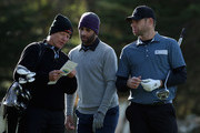 James Blake and his caddie discuss a tee shot, as Andy Roddick looks on during a practice round for the AT&T Pebble Beach National Pro-Am at Monterey Peninsula Country Club on February 5, 2014 in Pebble Beach, California.