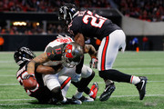 Mike Evans #13 of the Tampa Bay Buccaneers is tackled by C.J. Goodwin #29 and Keanu Neal #22 of the Atlanta Falcons during the second half at Mercedes-Benz Stadium on November 26, 2017 in Atlanta, Georgia.