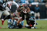 Doug Martin #22 of the Tampa Bay Buccaneers runs the ball against Luke Kuechly #59 and Charles Tillman #31 of the Carolina Panthers in the 1st quarter during their game at Bank of America Stadium on January 3, 2016 in Charlotte, North Carolina.