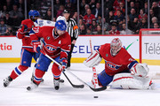 Andrei Markov #79 of the Montreal Canadiens picks up the loose puck in front of teammate Carey Price #31 during the NHL game against Tampa Bay Lightning at the Bell Centre on March 10, 2015 in Montreal, Quebec, Canada.  The Lightning defeated the Canadiens 1-0 in overtime.