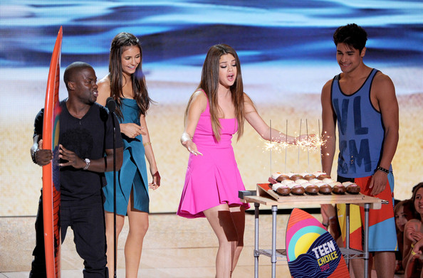 Singer Selena Gomez (2nd R) accepts the Choice Music Group award from actors Kevin Hart and Nina Dobrev onstage during the 2012 Teen Choice Awards at Gibson Amphitheatre on July 22, 2012 in Universal City, California.
