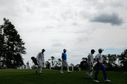 Webb Simpson (R) of the United States and Bubba Watson (2nd L) of the United States walk the fourth hole with their caddies Ted Scott (L) and Paul Tesori (2nd R) during a practice round prior to the start of the 2015 Masters Tournament at Augusta National Golf Club on April 6, 2015 in Augusta, Georgia.