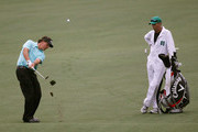 Phil Mickelson hits an approach shot as caddie Jim 'Bones' Mackay looks on during a practice round prior to the start of the 2012 Masters Tournament at Augusta National Golf Club on April 3, 2012 in Augusta, Georgia.